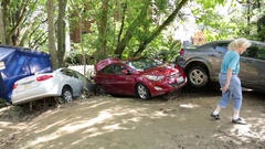 Woman walking by flood damaged cars piled on top of eachother, disaster. Panning Stock Footage