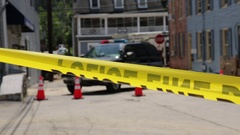 Police officer with lights flashing on their car, road block behind police tape Stock Footage