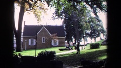 1970: a man in black dress walking in a garden area in front of the building Stock Footage