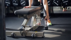 Woman finishes a workout and puts a free weight down near a flat bench Stock Footage