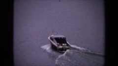 1970: a small, dark colored speedboat speeds across a river in a city WASHINGTON Stock Footage