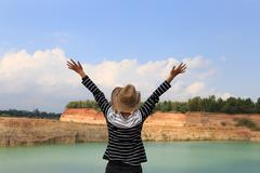 Woman raise her hands up feeling happy and free at orange hill and green pond Stock Photos