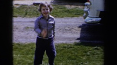 1959: a young short haired girl is running towards the camera in her yard  Stock Footage