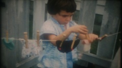 Little girl washes and hangs her dolls laundry, 3821 vintage home movie  Stock Footage