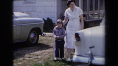 1959: a mother and her son walking past a car NEW YORK Stock Footage