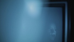 Zombie sees its reflection on a TV screen in a dark room Stock Footage
