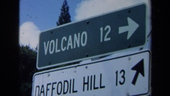 1969: two traffic signs showing direction and distance to a volcano and a hill Stock Footage