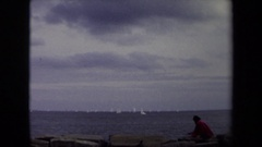 1970: a man in red shirt is playing in the sea side with many boats around Stock Footage
