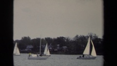 1970: dozens of sailboats on the water and older kids playing a game of football Stock Footage