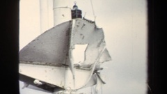 1970: tall white pole with waving red flag and ropes has bent metal plate  Stock Footage