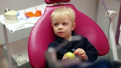 A small child in the dental chair. Cute child with apple in the dental office. Stock Footage