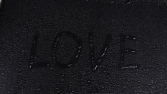 Word LOVE exposed to rain Stock Footage