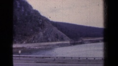 1959: panorama of a road with cars, a steep lapidarian slope adjacent Stock Footage