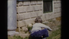 1959: a child sits on a patio next to two large metal jars NEW YORK Stock Footage