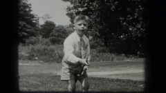 1939: a boy dressed in formal summer attire picks up a stick and uses it  Stock Footage