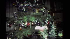1981: christmas tree loaded with tinsel in a living room with many presents Stock Footage