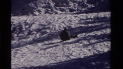 1981: person sliding short way down slope on small disc and then slowly falling Stock Footage