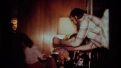 1984: family gathering, man and woman attempt to put together electronic item Stock Footage