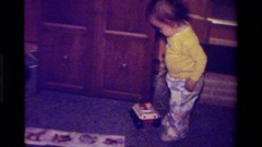 1979: child pulling a toy inside a furnished room and walking with the toy Stock Footage