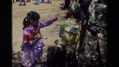 1985: a little girl in a purple shirt places a dollar in a bin DAFFODIL HILL Stock Footage