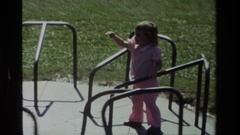 1979: a little brunette girl is being spun around slowly on a merry go round by Stock Footage