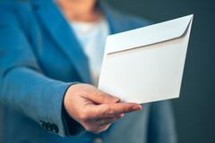Business woman offering white envelope as bribe Stock Photos