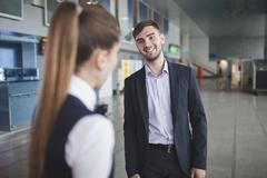 Young businessman smiling while looking at businesswoman at airport Stock Photos