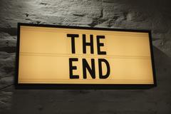 Close-up of The End signboard against gray wall Stock Photos