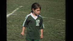 1981: a boy in green shirt is looking for his chance in a football game Stock Footage