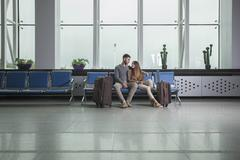 Young couple with luggage sitting on chairs at airport Stock Photos
