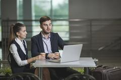 Young businessman with female colleague using laptop at table in airport Stock Photos