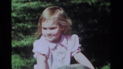 1979: a cute little girl in pink clothes rides a toy in a park CALIFORNIA Stock Footage