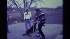 1976: small group of people in rural area gathered around dog, man on unicycle Stock Footage