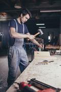Carpenter using hammer and chisel on timber at workshop Kuvituskuvat