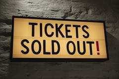 Close-up of Tickets Sold Out signboard against gray wall Stock Photos