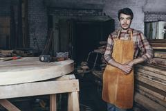 Portrait of carpenter standing by timber stack in workshop Stock Photos