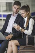 Young business couple using smart phone while waiting at airport Stock Photos
