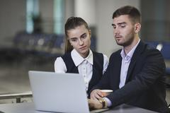 Young businessman and businesswoman using laptop at table in airport Stock Photos