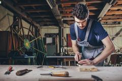 Carpenter using chisel on plank of wood in workshop Stock Photos