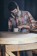 Man using electric sander on wood at workshop Stock Photos