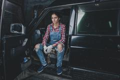 Portrait of confident female mechanic sitting in car at workshop Stock Photos