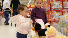 Children watch robotic playing toys in action in a big supermarket for kids Stock Footage