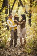 Full length of parents looking at baby boy in park during autumn Stock Photos