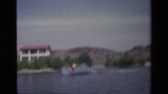 1977: sea spray shoots behind a motor boat as it pulls a jet skier CANYON LAKE Stock Footage