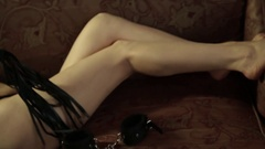 Seductive Woman lying on a couch, holding whip. BDSM concept, accessories and Stock Footage