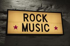Close-up of Rock Music signboard against gray wall Kuvituskuvat