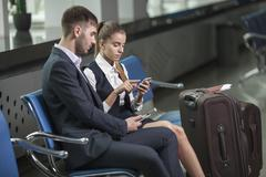 Young business couple using mobile phones while waiting at airport Stock Photos