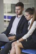 Young businesswoman sitting by businessman using laptop at airport Stock Photos