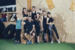 Portrait of confident male and female athletes flexing muscles at health club Stock Photos