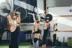 Side view of athletes lifting barbells at gym Stock Photos